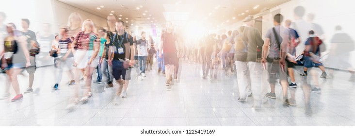 Crowd of anonymous people walking on trade show