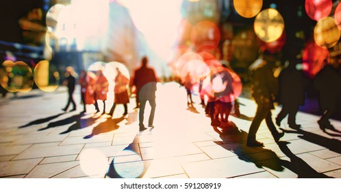 Crowd of anonymous people walking on sunny streets in the city