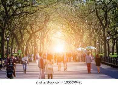 Crowd of anonymous people walking through Central Park forest landscape with bright sunlight shining through the trees in the background