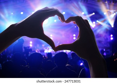 Crowd of Audience at during a concert with silhouette of a heart shaped hands shadow