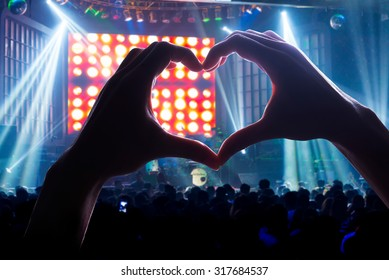 Crowd Audience the power of music, silhouette heart shaped hands shadow