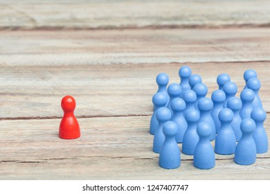 a crowd of blue pawns, one red pawn in the middle, on a wood table. grey background, studioshot.