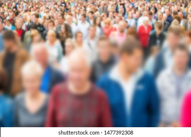 Crowd of blurred people walking on busy city street