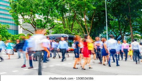 Crowd of business people crossing road in Singapore downtown. motion blur, panorama