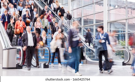 Crowd of business people on escalator on a business trade fair
