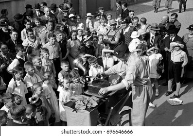 Crowd of children and adults listening to music from gramophone during party or festival