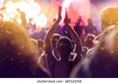 Crowd at concert and colorful stage lights - summer music festival concept