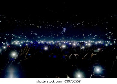 Crowd at concert with lights and camera flash on