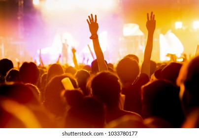 Crowd of concert stage lights and people fan audience silhouette raising hands or glow stick holding in the music festival rear view with spotlight glowing effect