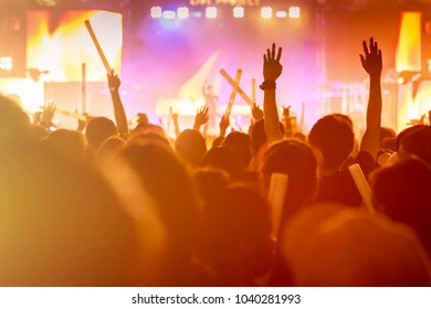 Crowd of concert stage lights and people fan audience silhouette raising hands or glow stick holding in the music festival rear view with spotlight glowing effect and smoke