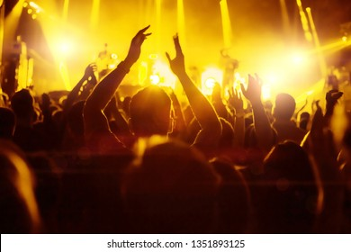 Crowd of fans at concert at music festival,  silhouettes of raised hands with yellow backlight flare.