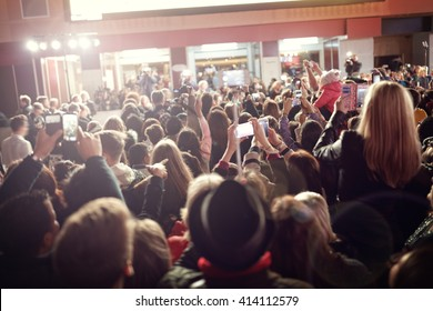Crowd and fans taking photographs on mobile phones at a red carpet film premiere