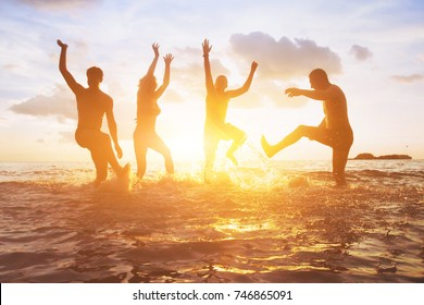 crowd of friends having fun in the water at sunset, silhouettes of happy people enjoying summer holidays