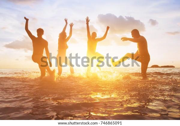 Menge Freunde, die sich bei Sonnenuntergang im Wasser amüsieren, Silhouetten von glücklichen Menschen, die die Sommerferien genießen