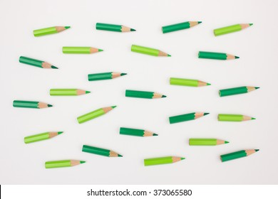 Crowd of green colored pencils pointing in the same direction - abstract image visualizing leadership, business strategy, dynamic movement