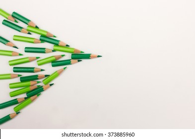 Crowd of green pens pointing to the right - team workshop, strategy, success, leadership concept with space for copy text