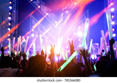 Crowd of hands up concert stage lights and people fan audience silhouette raising hands or glow stick holding in the music festival rear view with spotlight glowing effect nightlife event.