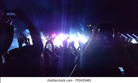 Crowd hands up at night concert with blurry background