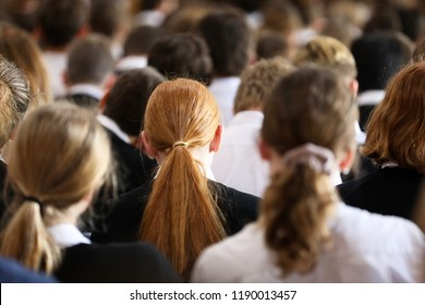 Crowd of high school students in uniform at assembly listening and facing forward. Red haired long hair female girl student in focus. Education teacher pedagogy system concept.