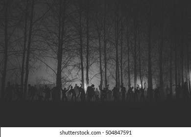 crowd of hungry zombies in the woods. Silhouettes of scary zombies walking in the forest at night. Black and white version