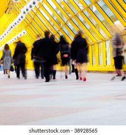 Crowd move in modern yellow corridor