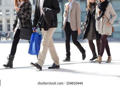 A crowd moving against a background of an urban landscape. Young people. Motion blur. Walking businessmen against a background of an urban landscape.