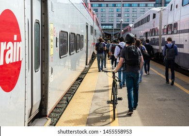 Crowd of passengers walking on outdoor train platform toward station exit after disembarking Caltrain cars at commuter rail line terminus - San Francisco, California, USA - July 12, 2019