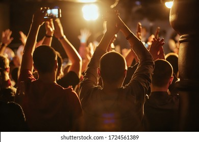 A crowd of people with backs jumping and clapping their hands in the rays of yellow light.