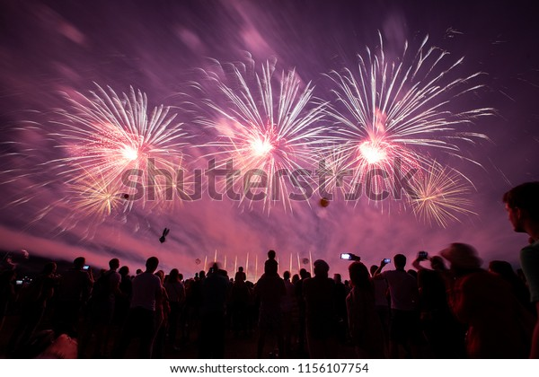 a crowd of people came to the festival, a festival of fireworks, explosions of pyrotechnic charges, volleys of salutes against the backdrop of happy people rejoicing in the beautiful spectacle, multic