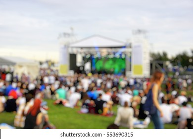 A crowd of people at a concert in the park. Near the scene. Blurred background