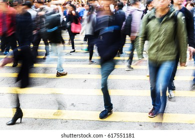 crowd of people crossing a city street in motion blur
