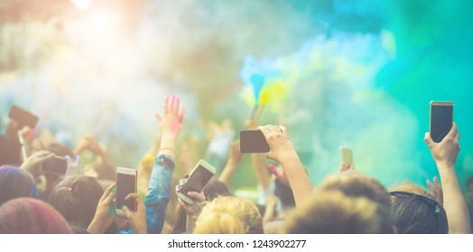 Crowd of people dancing and celebrating Holi festival of colors. People taking photos with mobile phones at color festival