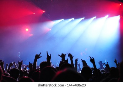 A crowd of people dancing at a musical rock concert under the light and smoke of spotlights