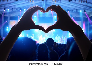 Crowd of people at during a concert  with a heart shaped hand shadow