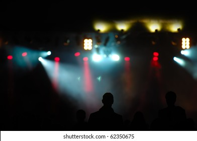 Crowd of people in front of spotlights at a concert.