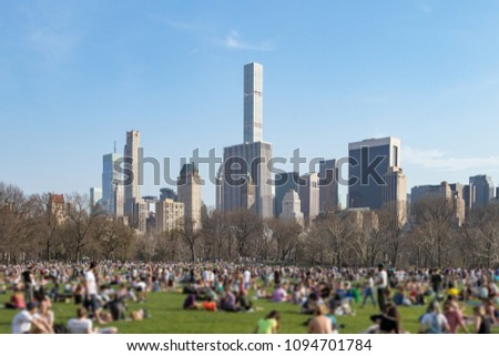 Crowd of people gathered on the Great Lawn in Central Park on a sunny day with the Manhattan skyline of New York City in the background