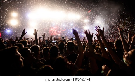 Crowd of people having fun while watching confetti fireworks at music festival. Copy space.