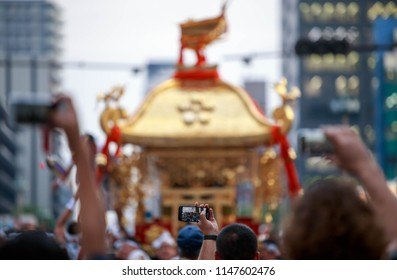 Crowd of people holding phones high to take pictures of golden portable shrine at summer festival in Japan