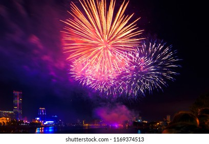 crowd of people looking at Red, white and gold fireworks ver the sea with blue twilight sky background and city view