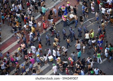 Crowd of people moving around in the  street carnival at São Paulo, Brazil, as a group of gray uniformed police pass by