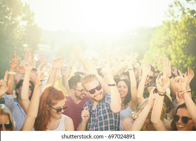 Crowd of people at music festival dancing and enjoying music