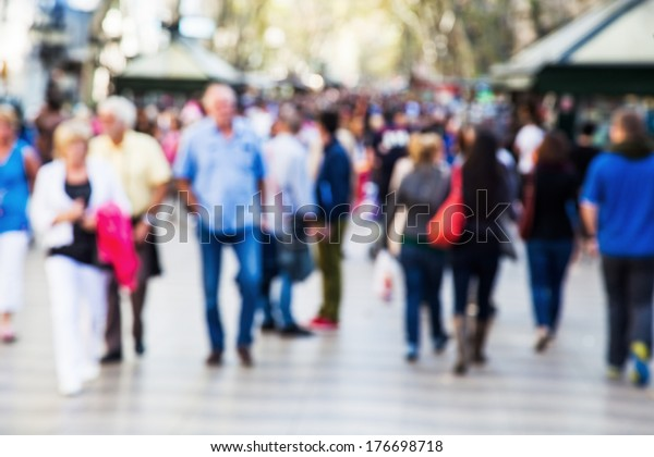 crowd of people out of focus on a strolling promenade