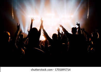 Crowd of people with raised up hands to the stage. Bright stage light silhouettes