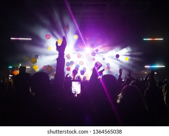 A crowd of people raising their arms up during a concert. They are enjoying the music