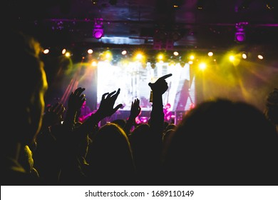 A crowd of people raising their arms up during a concert. They are enjoying the music. Selective focus.