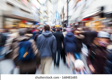 crowd of people in the shopping street of a city with intentional zoom effect