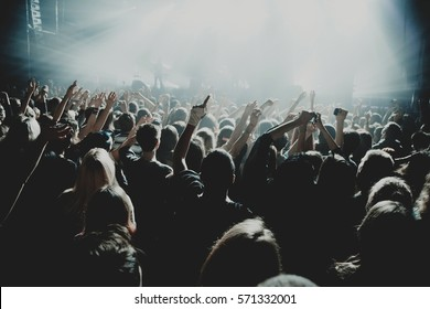 crowd of people silhouettes with their hands up during the concert. Dark background, smoke, concert  spotlights