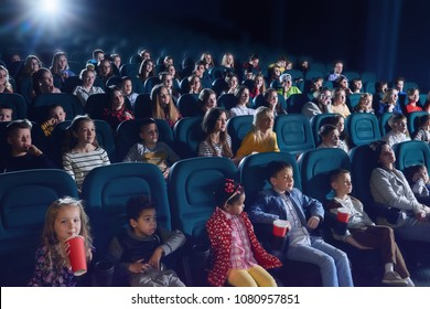 Crowd of people sitting in comfortable seats in modern movie theatre. Children, teens, adults watching  film and sipping fizzy drinks. Concept of cinematography and entertainment.