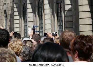 Crowd of people standing outside a building in the sunshine taking photographs on camera and mobile devices viewed from behind