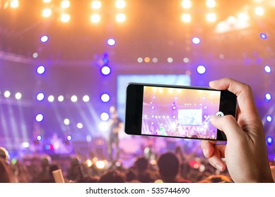 Crowd people use smart phones take photo at music concert